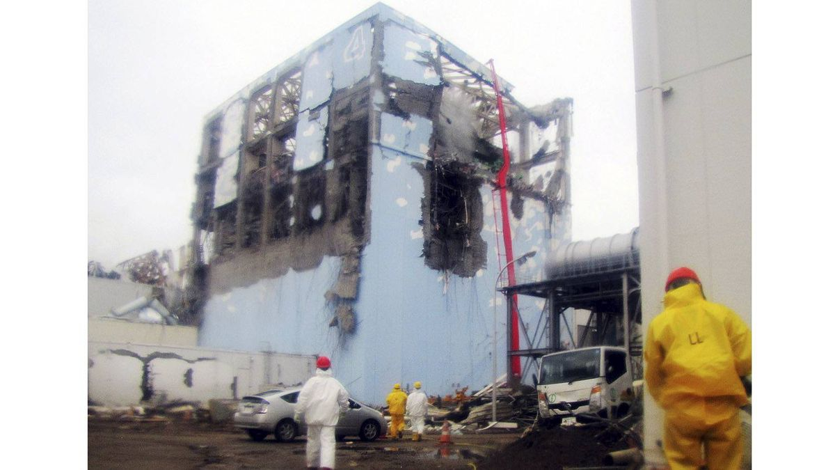 In this photo released by Tokyo Electric Power Co. (TEPCO) via Kyodo News, workers in protective suits conduct cooling operation by spraying water at the damaged No. 4 unit of the Fukushima Dai-ichi nuclear complex in Okuma, northeastern Japan,Tuesday, March 22, 2011.