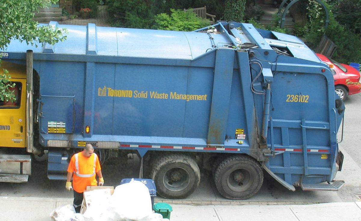 The sight of Garbage truck in front of my house today - the civic worker is obviously shocked at the pile of recycling materials that have been collecting in my porch (mostly boxes and Styrofoam).