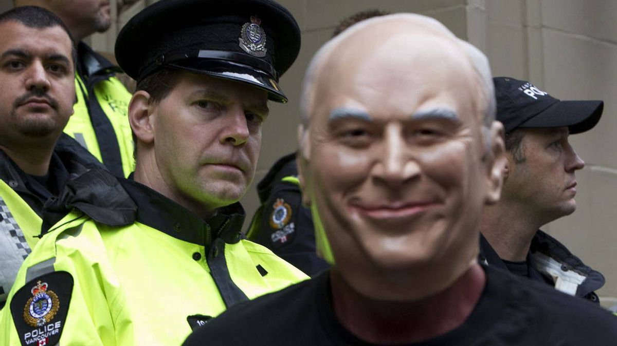 A protester wearing a Dick Cheney mask stands in front of a police line during a demonstration against the former U.S. vice-president's speaking engagement at the Vancouver Club on Sept. 26, 2011.