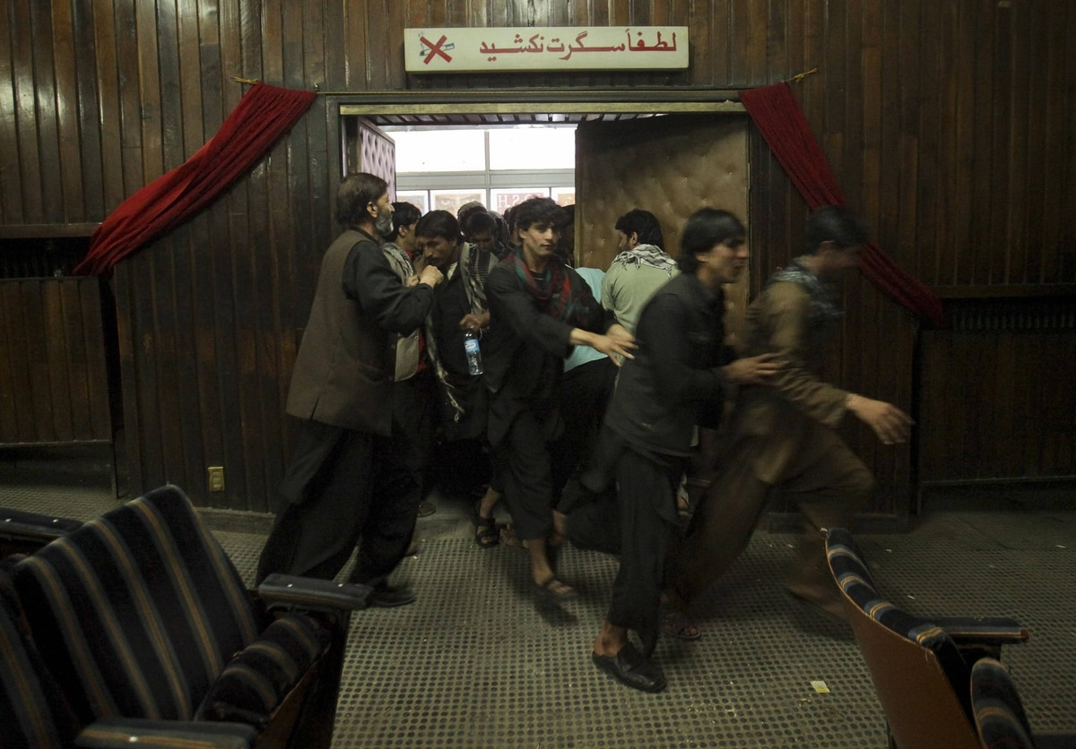 Cinema goers rush into the theater before a show at Pamir Cinema in Kabul.