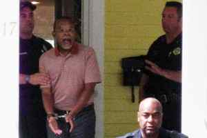 In this photo taken by a neighbour on July 16, 2009, Henry Louis Gates Jr., centre, the director of Harvard University's W.E.B. DuBois Institute for African and African American Research, is arrested at his home in Cambridge, Mass.