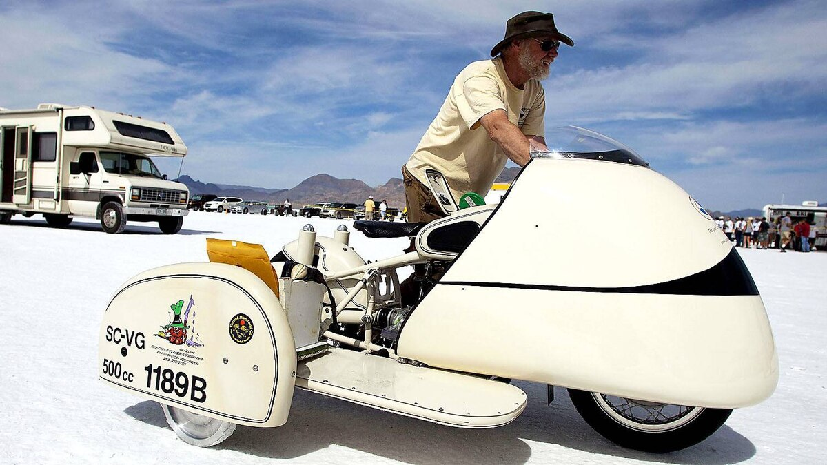 Kevin Brooks pushes his vintage BMW motorcycle to be inspected during the first day of the 63rd annual Bonneville SpeedWeek.