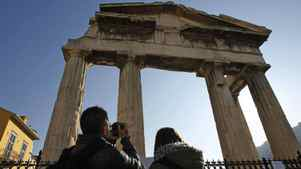 Tourists stand outside the closed gate of the Roman Agora during a 24-hour strike in Athens, Thursday, Dec. 1, 2011.