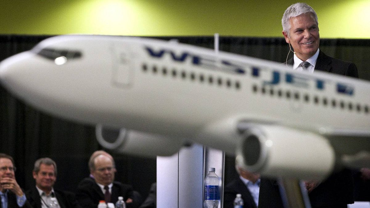 Gregg Saretsky, right, president and CEO of WestJet, turns to watch a video while addressing the company's annual meeting in Calgary, Tuesday, May 3, 2011.