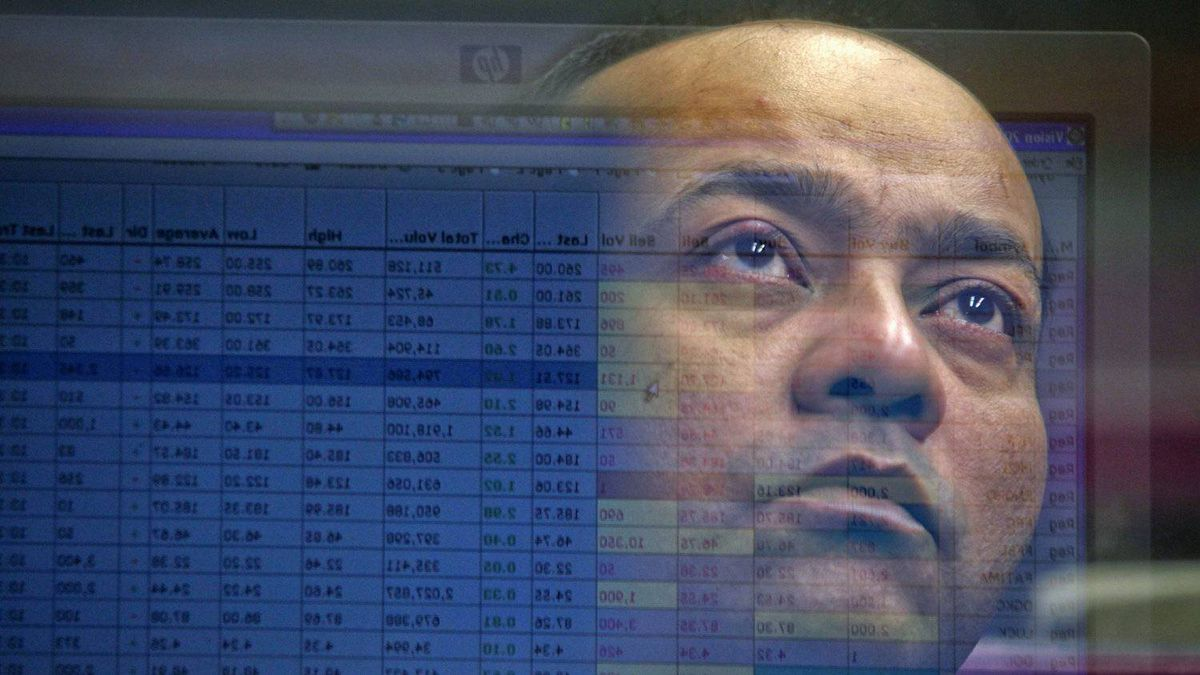 A computer screen displaying stock information is reflected in the window of a booth where a broker is monitoring the markets at Karachi's Stock Exchange Feb. 6, 2012.