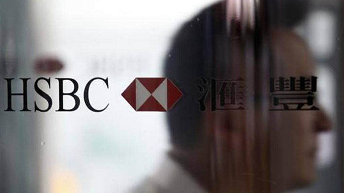 A man walks past the HSBC logo at the bank's headquarters in Hong Kong September 8, 2011.