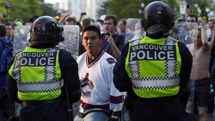 A Vancouver Canucks fan confronts the police during riots after the Canucks lost Game 7 of the NHL Stanley Cup final hockey game to the Boston Bruins in Vancouver, British Columbia June 15, 2011.