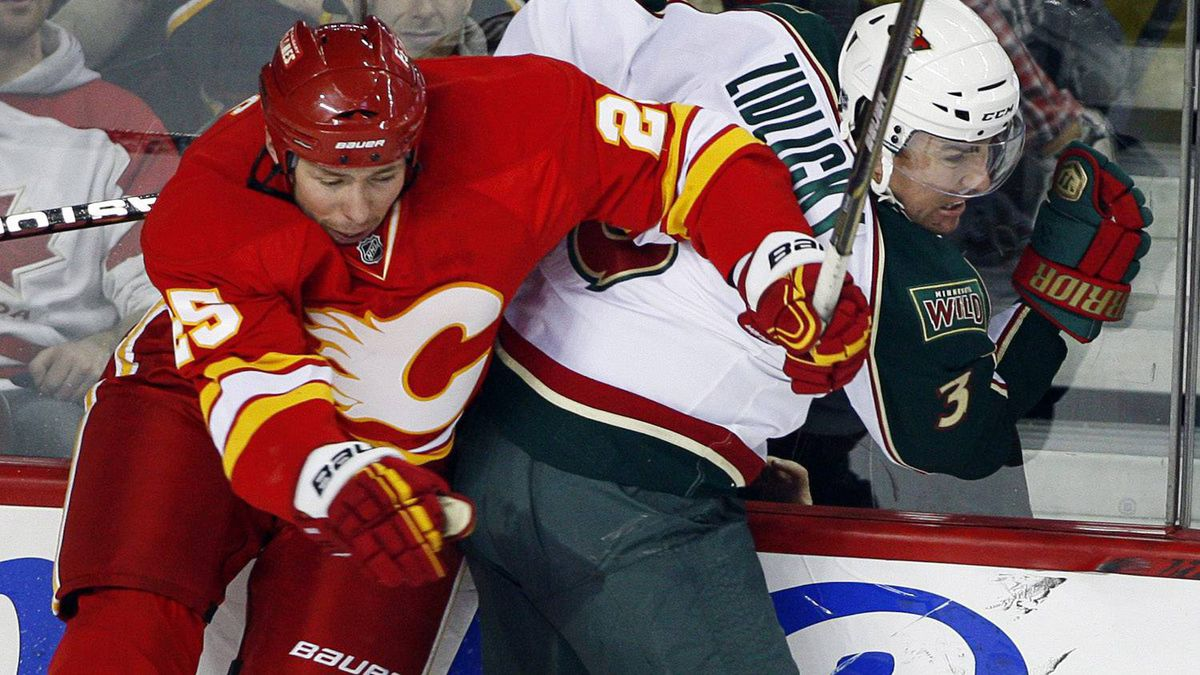 Minnesota Wild's Marek Zidlicky, right, from the Czech Republic, and Calgary Flames' David Moss leave the ice as they collide during second period NHL hockey action in Calgary, Alta., Saturday, Dec. 18, 2010. The Wild won 3-1. THE CANADIAN PRESS/Jeff McIntosh