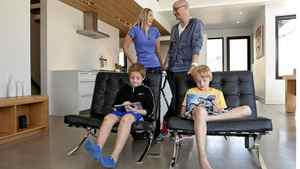 Melissa and Geoff Teehan and their children Sam (left front) and Cole, in their new accessible home in the Beaches neighbourhood of Toronto. They built the home after Melissa suffered a sudden illness and became paralyzed.