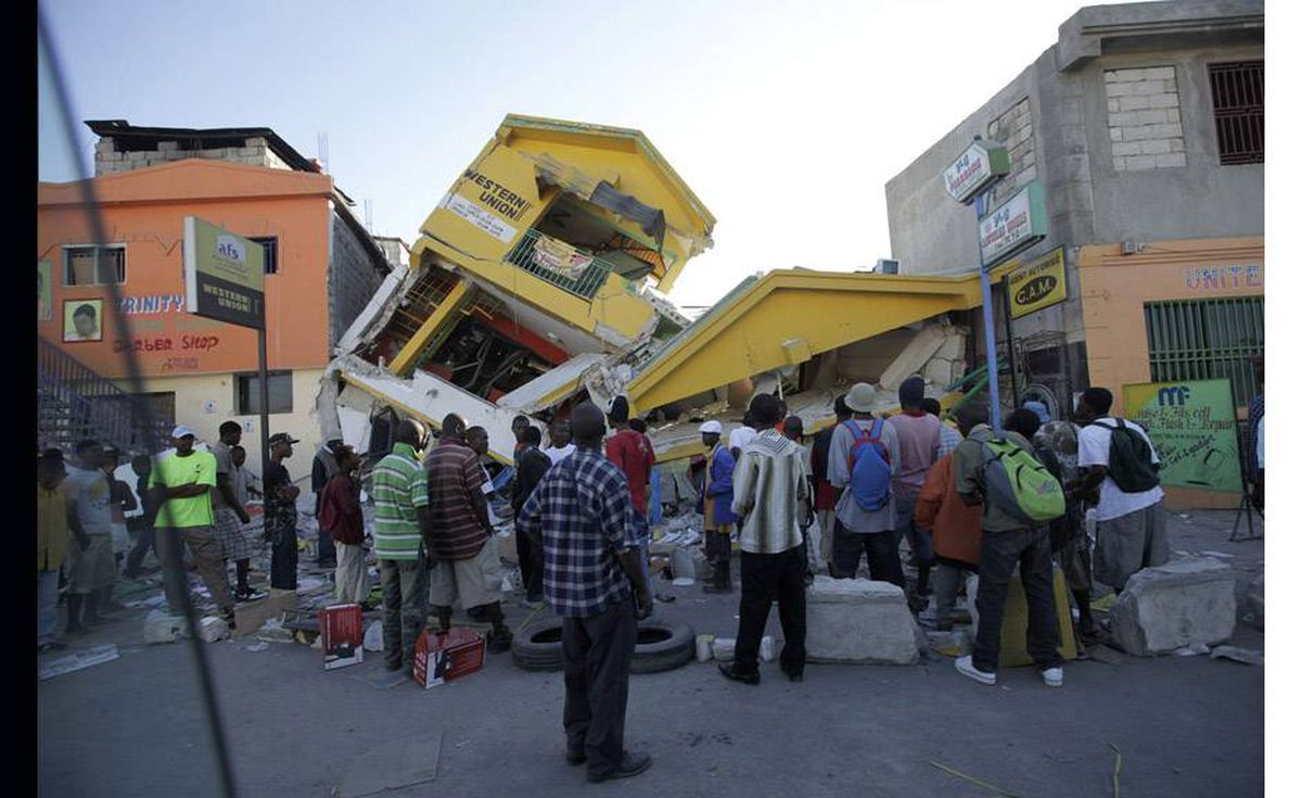 People look at a destroyed building in Port-au-Prince January 14, 2010. The death toll from Haiti's earthquake could be between 45,000 and 50,000, with a further three million people hurt or homeless, a senior Haitian Red Cross official said on Thursday.