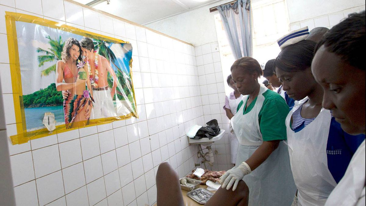 Staff and trainees wait patiently during the labour of Santo Sesay, 20. Delivering her child is midwife Elizabeth Bangali, in green, and a group of students. Sesay gave birth to a healthy 2.58 kg baby boy.