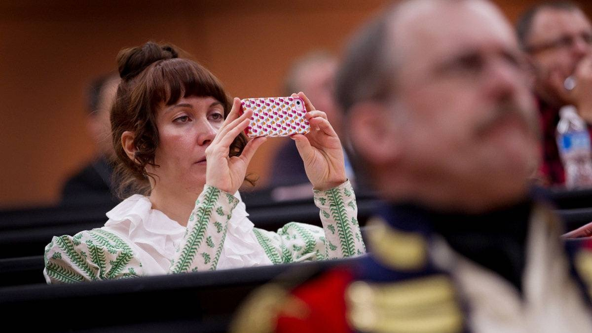 Tonya Staggs, of Nashville, Tenn., who had been one of the models for period dresses in an earlier lecture, takes photographs with her smart phone during a class on British and Canadian uniforms 1812-1814.