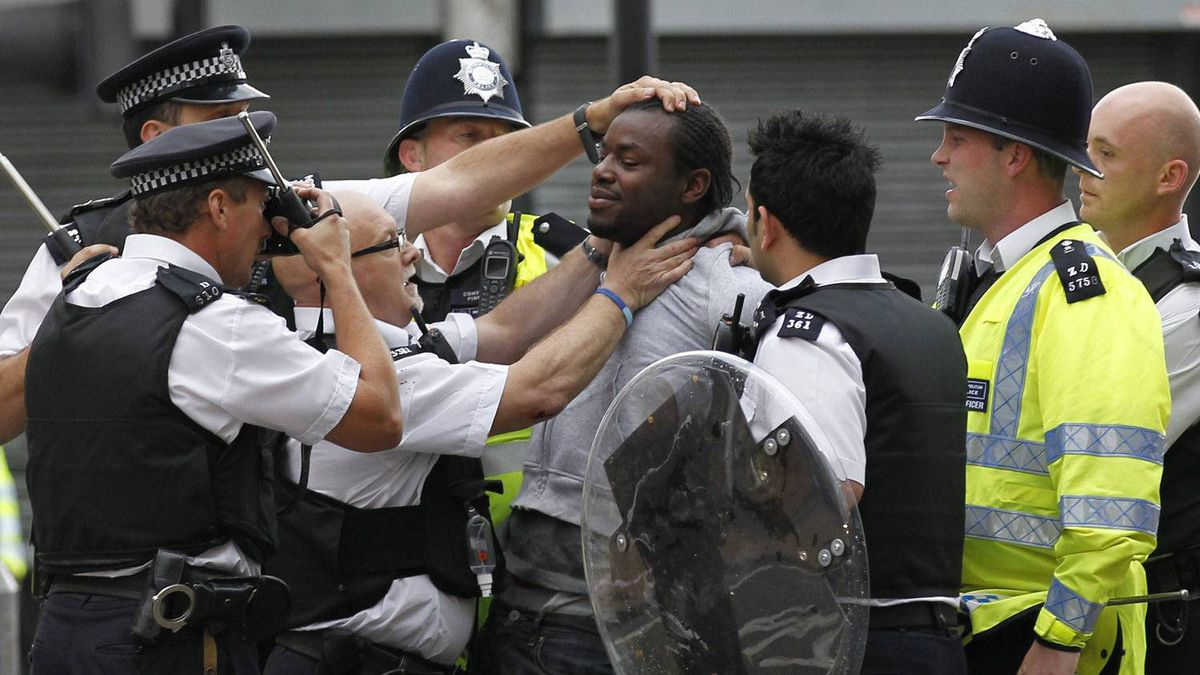 British police officers arrest a man as rioters gathered in Croydon, south London, Monday, Aug. 8, 2011. Violence and looting spread across some of London's most impoverished neighborhoods on Monday, with youths setting fire to shops and vehicles, during a third day of rioting in the city that will host next summer's Olympic Games.