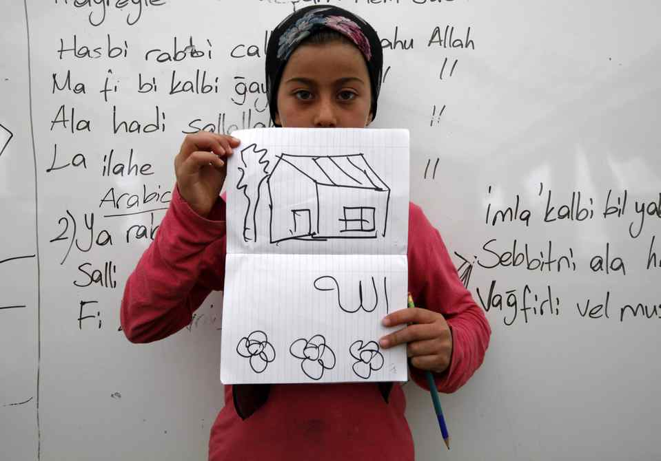Edibe Hirfan,10, a Syrian refugee, shows a drawing of her dream home during a class at a school for refugee children at Boynuyogun refugee camp in Hatay province near the Turkish-Syrian border.