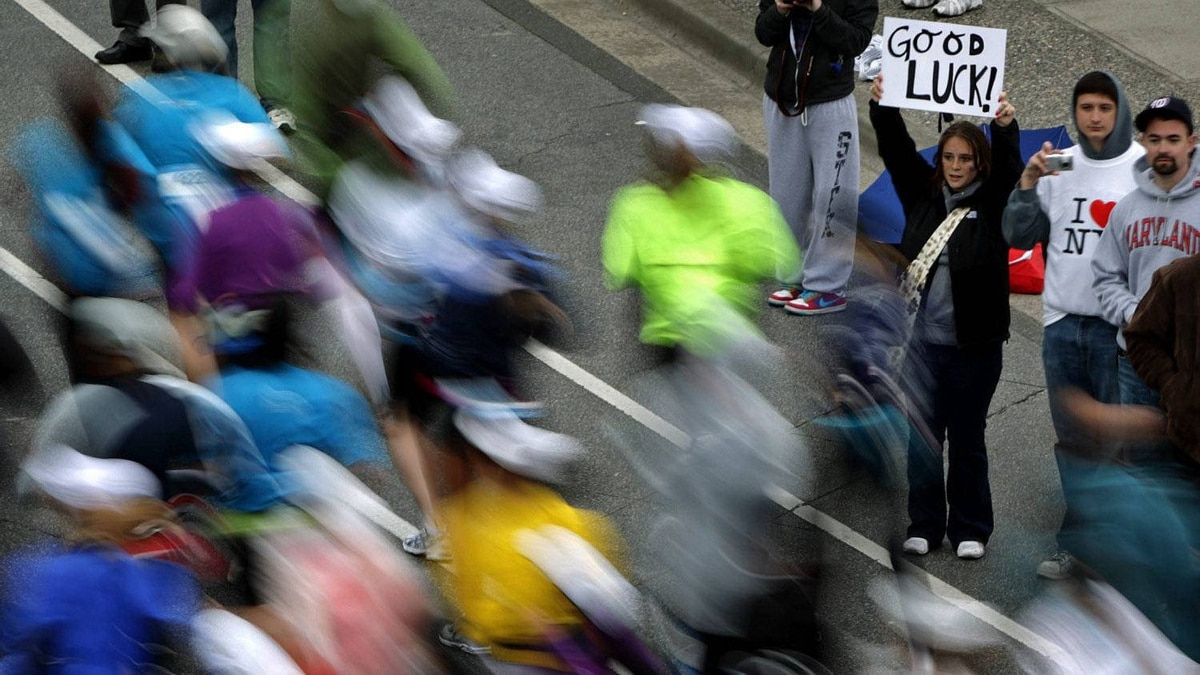 A spectator holds up a sign wishing runners good luck as they race past during the BMO Vancouver Marathon in Vancouver, B.C., on Sunday May 2, 2010.