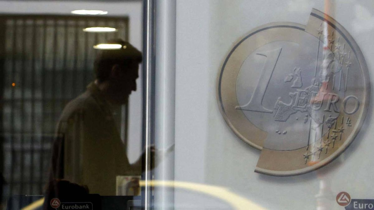 A pedestrian is reflected on the window of a bank branch in central Athens on Tuesday.