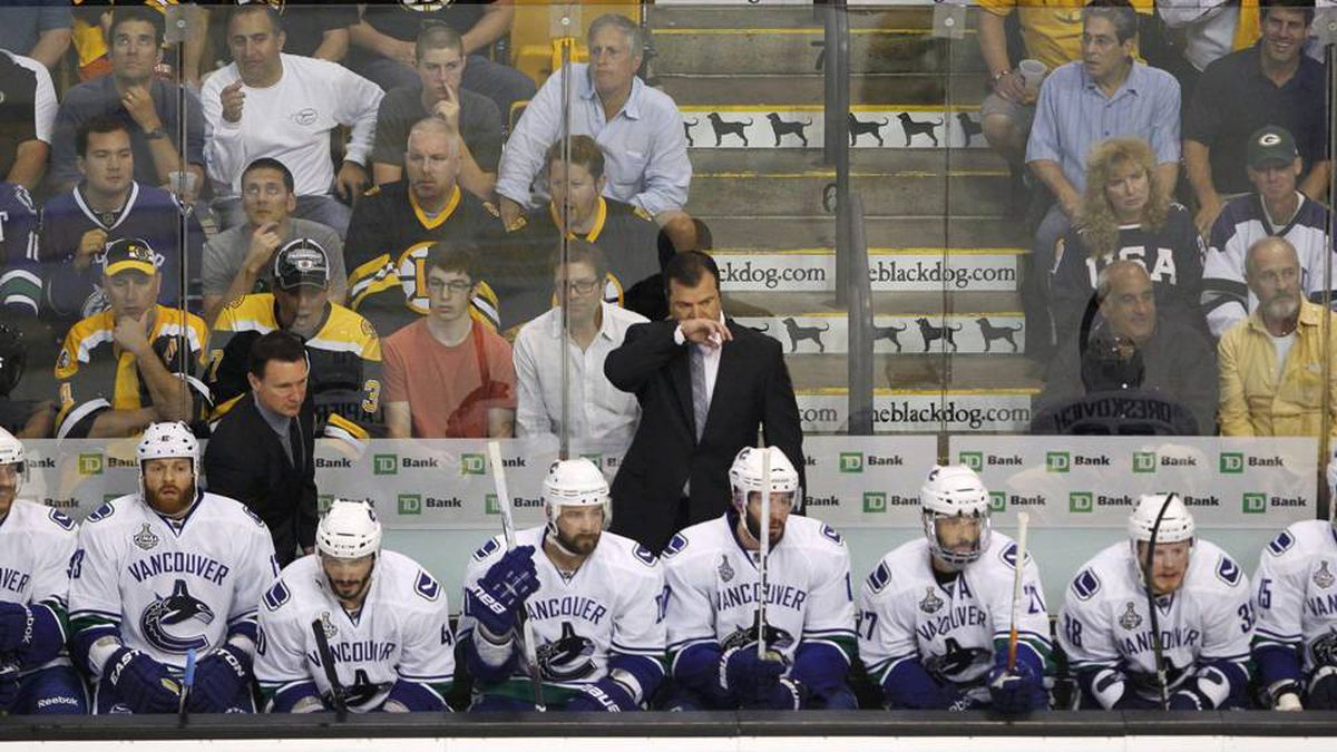 Vancouver Canucks head coach Alain Vigneault stands behind the bench as his team plays the Boston Bruins in Game 4.