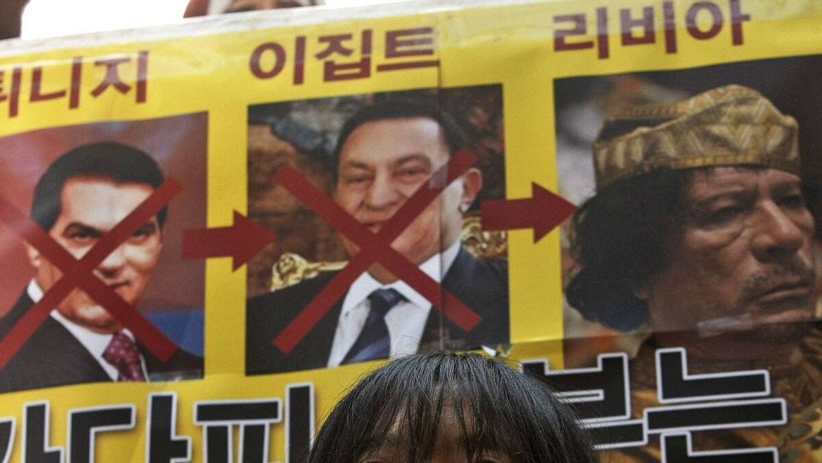 A South Korean college student stands under photos of Tunisian President Zine al-Abidine Ben Ali, left, Egyptian President Hosni Mubarak and Libyan leader Moammar Gadhafi, right, during a rally to support the democracy movement in Libya, in front of the Libyan embassy in Seoul, South Korea, Wednesday, Feb. 23, 2011.
