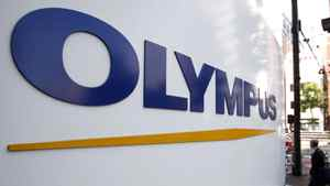 A man walks past a sign of Olympus Corp outside the company's showroom in Tokyo November 4, 2011.