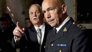 Minister of Public Safety Vic Toews calls on a reporter as newly appointed RCMP Commissioner Bob Paulson takes questions in the foyer of the House of Commons on Nov. 16, 2011.