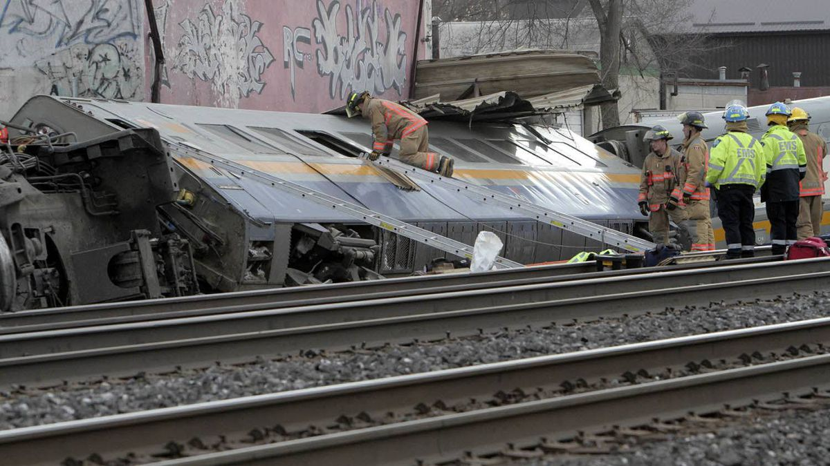 Rescue workers climb on an overturned Via Rail car Sunday February 26, 2012.