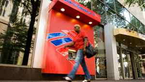 A pedestrian walks past a Bank of America ATM in Charlotte, North Carolina July 17, 2009.