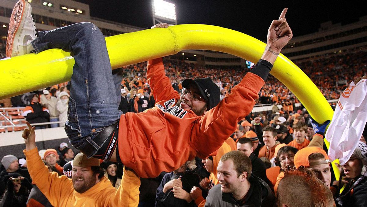 Oklahoma State Cowboys fans hang on the goalpost after a 44-10 win against the Oklahoma Sooners at Boone Pickens Stadium on December 3, 2011 in Stillwater, Oklahoma. (Photo by Ronald Martinez/Getty Images)