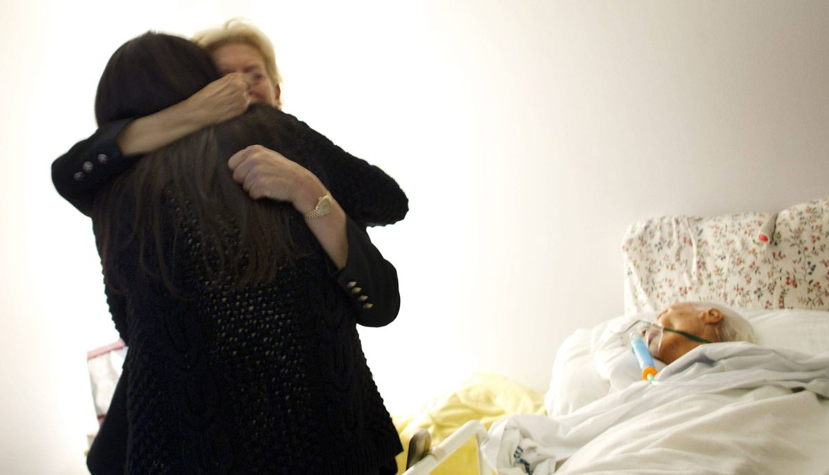 Basia Hoffman hugs Kensington Hospice Social Worker Maxxine Rattner as her mother, Andree Hoffman, lays in bed at Kensington Hospice in Toronto. Andree Hoffman passed away that night at 4:44am.
