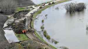 Workers shore up the swollen Assiniboine River on May 11, 2011.
