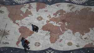 Pedestrians in Lisbon cross a square decorated with a giant world map. In recent years, Portugal has been a magnet for immigrants from its former colonies and other African nations but as Lisbon struggles to navigate the turbulent straits of the euro zone crisis, that trend has been reversed.