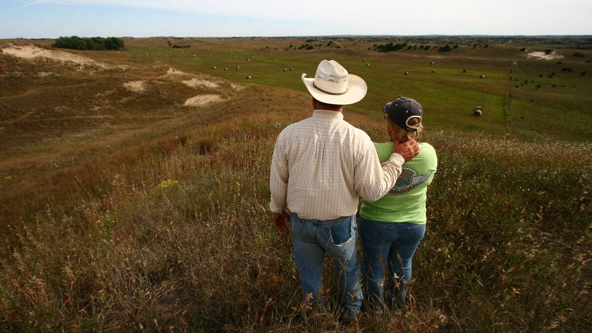 Lin and Marie Gumb look out over their ranch in the Nebraska Sandhills, where grasses grow over top of a vast plain of sand and dune.