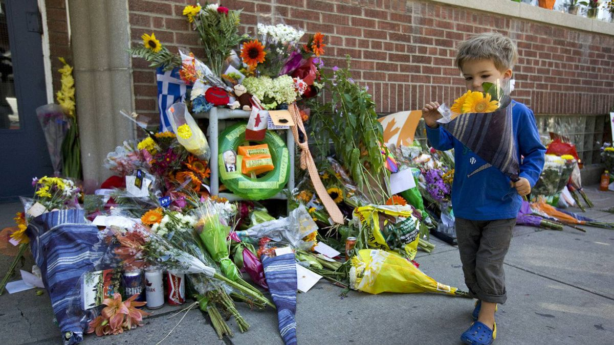 A toddler holds a boquet of orange flowers at a memorial to Jack Layton outside the late NDP leader's Toronto constituency office on Aug. 23, 2011.