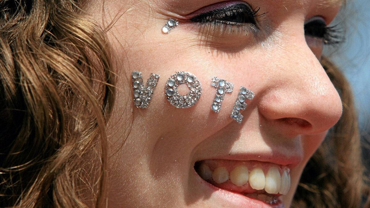 Miss Teen London, Kelsey Johnson, 18, wears a message on her cheek at a gathering in London, Ont., on Sat.