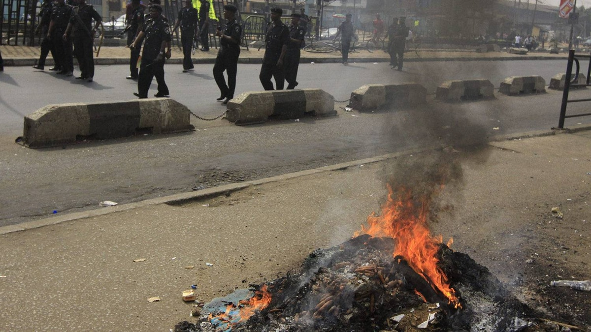 Policemen walk past burn barricades set alight by protesters following the removal of a fuel subsidy by the government in Lagos, Nigeria, Monday, Jan. 9, 2012. A national strike paralyzed much of Nigeria on Monday, with more than 10,000 demonstrators swarming its commercial capital to protest soaring fuel prices and decades of government corruption in the oil-rich country.