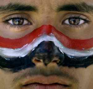 An anti-government protestor with the colours of his national flag painted on his face, during a demonstration demanding the resignation of Yemeni President Ali Abdullah Saleh, in Sanaa,Yemen, Thursday, March 24, 2011.