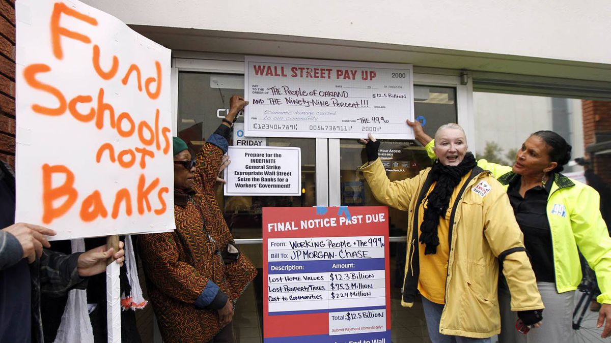 """Anti-corporate demonstrators put signs up on a bank Nov.19, 2011 in Oakland, Calif. Occupy Oakland protesters, calling for a """"mass day of action,"""" took over a vacant lot in downtown Oakland, claiming it as their new encampment."""