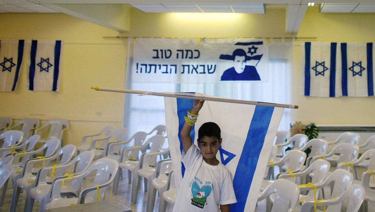 A boy holds an Israeli flag in front of a banner depicting captured Israeli soldier Gilad Shalit at a community centre in the village of Mitzpe Hila, northern Israel.