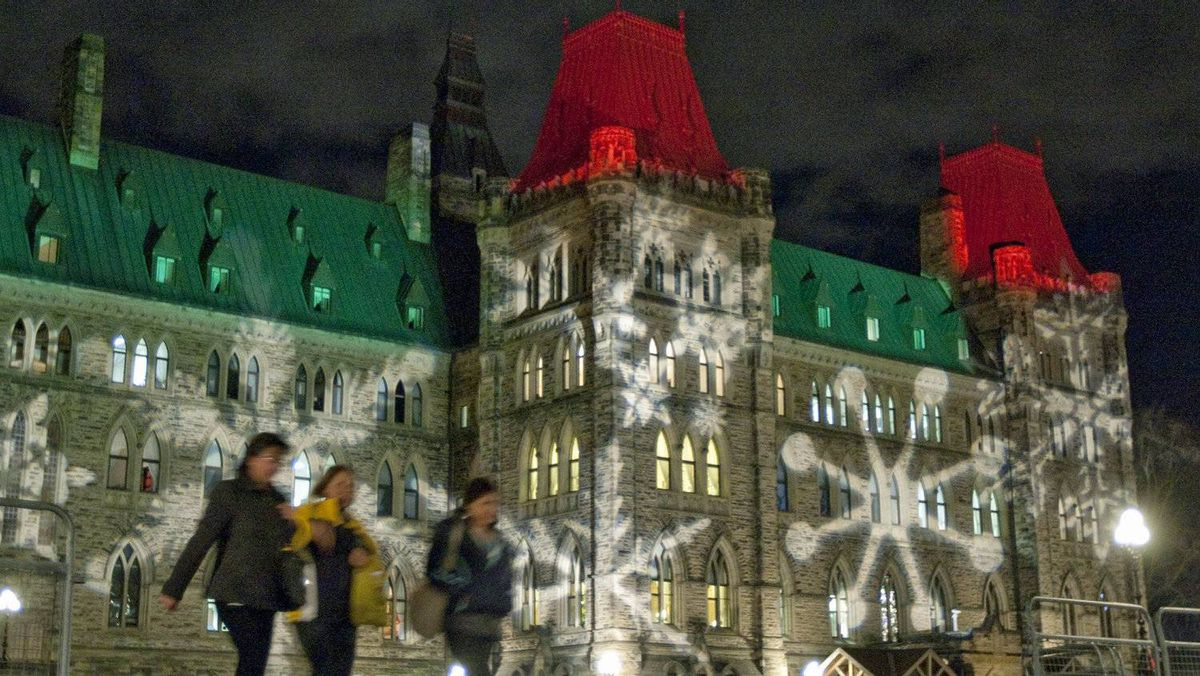 Pedestrians leave Parliament Hill as the National Capital Commission tests its Christmas lighting on Nov. 28, 2011.