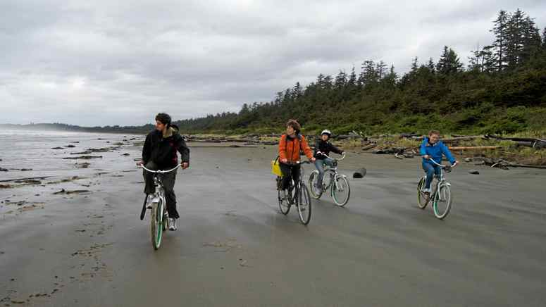 The writer (in orange), her daughter (in blue) and friends cycle Long Beach as high tide approaches.