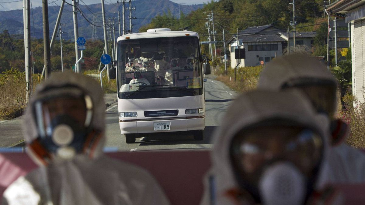 Japanese officials wearing protective suits and masks ride in the back of a bus while a second bus carrying officials and journalists follow as they drive through the contaminated exclusion zone on their way to the crippled Fukushima Daiichi nuclear power plant in Fukushima prefecture November 12, 2011.