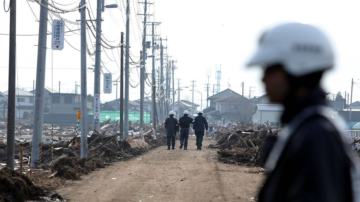 Police officers walk towards a residential area damaged by the tsunami after an 8.9 magnitude strong earthquake struck on March 11 off the coast of north-eastern Japan, on March 13, 2011 in Sendai, Japan. The quake struck offshore at 2:46pm local time, triggering a tsunami wave of up to 10 metres which engulfed large parts of north-eastern Japan. The death toll is currently unknown, with fears that the current hundreds dead may well run into thousands.