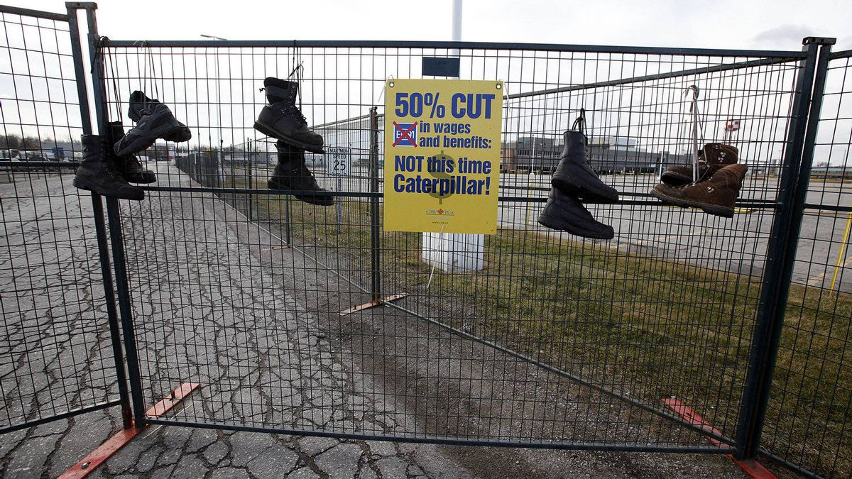 Electro-Motive Canada employees' work boots hang on the fence on the picket line outside the subsidiary of Caterpillar in London on Feb. 8.
