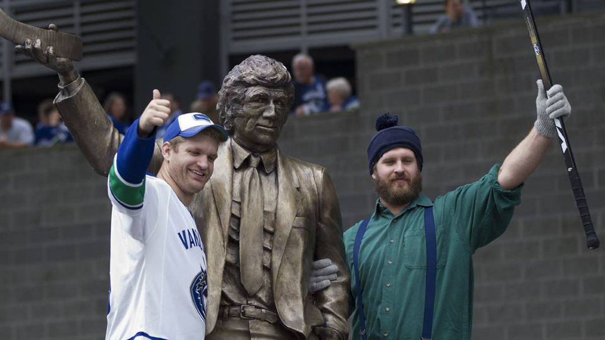 Vancouver Canuck fans with a statue of former coach Roger Neilson outside Rogers Arena before the start Game 5.