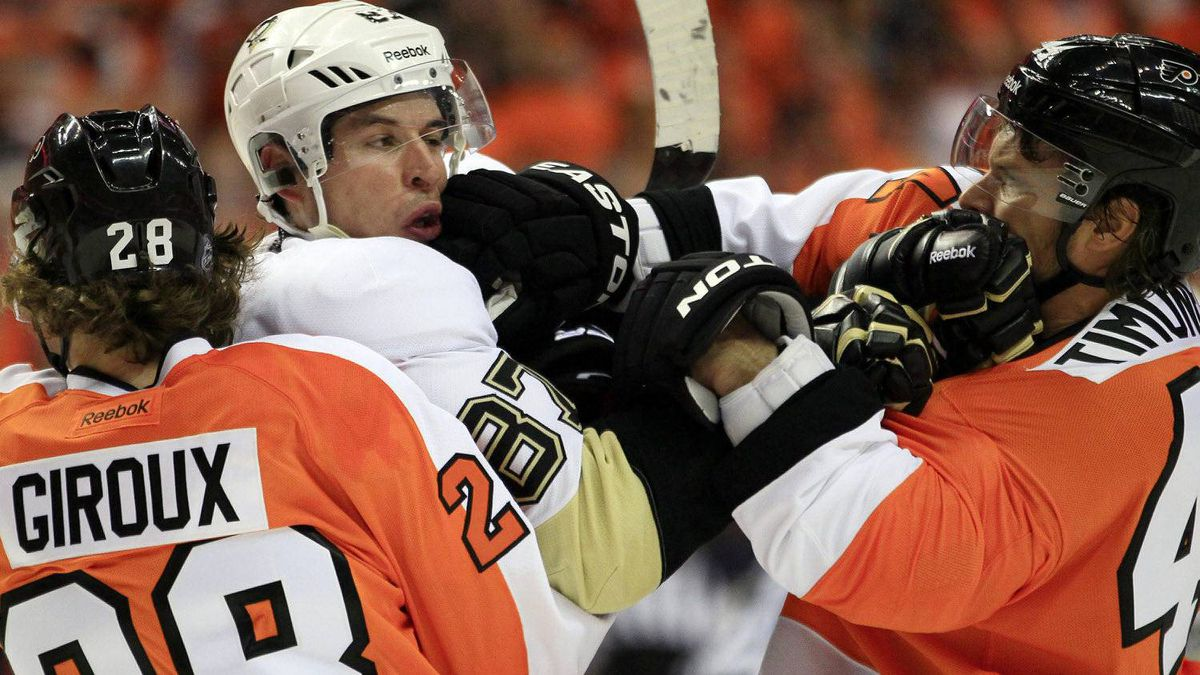 Philadelphia Flyers Claude Giroux, left, holds on to Pittsburgh Penguins Sidney Crosby as Kimmo Timonen, right, lands a punch to Crosby's jaw during the first period of Game 3 in a first-round NHL Stanley Cup playoffs hockey series, Sunday, April 15, 2012, in Philadelphia. (AP Photo/Tom Mihalek)