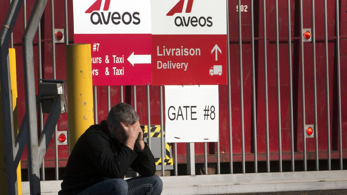 A laid off Aveo employee makes a call in front of the aircraft maintenance company's plant Tuesday, March 20, 2012 in Montreal.