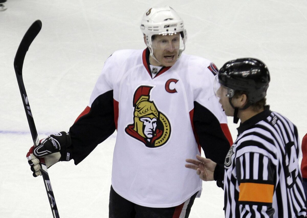 Ottawa Senators right winger Daniel Alfredsson, left, argues a call with referee Brad Meier during an NHL hockey game.