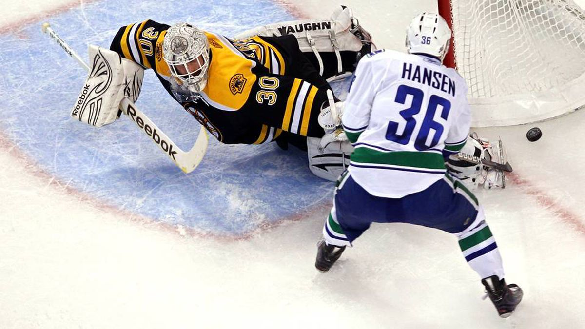 Jannik Hansen of the Vancouver Canucks takes a shot against Tim Thomas of the Boston Bruins during Game 6.