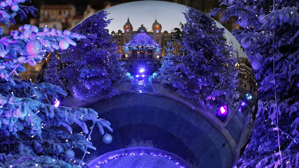 Monte Carlo casino is reflected in a mirror between Christmas trees in Monaco.