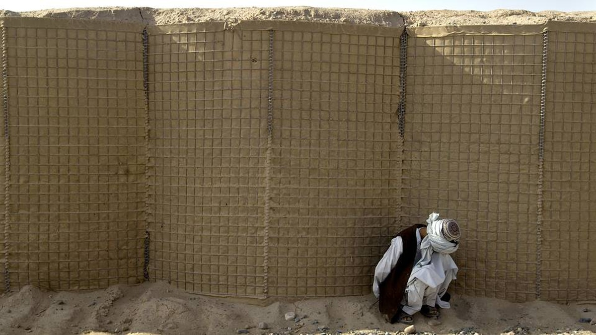 A detainee captured by the Afghan Army on a joint patrol with Canadian troops sits by a wall at a Canadian Forward Operating Base in Howz E Madad in Zhari District, Kandahar Province, Afghanistan.
