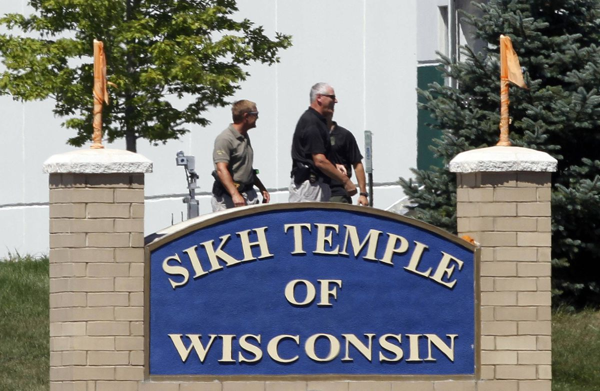 Officials gather near the Sikh Temple in Oak Creek in Wisconsin August 5, 2012 following a mass shooting inside and outside the Sikh Temple. A shooting during Sunday services at a Sikh temple left at least seven people dead, including a gunman, and at least three critically wounded, police and hospital officials said.